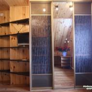 Шкаф-купе для гардеробной выполнен из сосны. Раздвижные двери облицованы зеркалом и стеклом с рисунком.